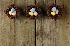 Chocolate nests with candy eggs on rustic wood Royalty Free Stock Photography