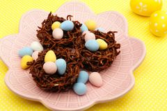 Chocolate nests with Easter eggs on yellow Stock Image