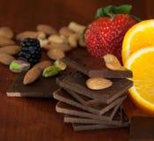 Chocolate, nueces, bayas y naranja Imágenes de archivo libres de regalías