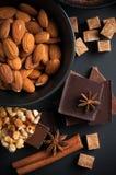 Chocolate, nueces, dulces, especias y azúcar marrón Foto de archivo libre de regalías