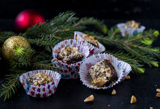 Chocolate-nut sweets with honey. On a black background with the decoration of fir branches and Christmas Ornaments Stock Photo