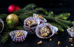 Chocolate-nut sweets with honey. On a black background with the decoration of fir branches and Christmas Ornaments Royalty Free Stock Image