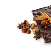 Chocolate and nuts with cinnamon sticks, star anise Royalty Free Stock Photos