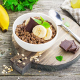 Chocolate oatmeal for breakfast with slices of a ripe banana and pieces of bitter good chocolate in a white ceramic bowl Royalty Free Stock Photos