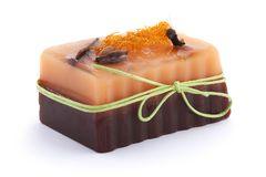 Chocolate orange soap with clove, Illicium, cinnamon and loofah on top  on white background Stock Photo