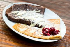 Two pancakes on a white plate. Chocolate and ordinary pancake on a with plate. With cherry`s on top Royalty Free Stock Images