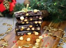 Chocolate oscuro con las avellanas en la decoración del Año Nuevo Fotografía de archivo