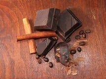 Chocolate oscuro con los granos del canela y de café imagen de archivo