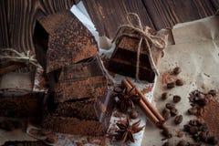 Chocolate oscuro en el documento sobre la tabla de madera con el grano de café, cacao Foto de archivo