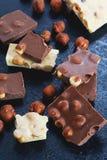 Chocolate oscuro y blanco con las avellanas en un fondo azul Foto de archivo