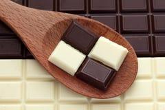 Chocolate oscuro y blanco en una cuchara de madera Fotos de archivo