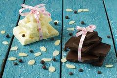 Chocolate, pétalos de la almendra y gotas de chocolate blancos y negros fotografía de archivo