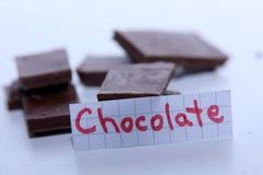 Chocolate, palabra inglesa en una nota blanca, pedazos de chocolate en fondo Imágenes de archivo libres de regalías
