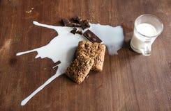 Chocolate, pan y leche derramada en la tabla Fotos de archivo