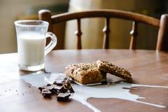 Chocolate, pan y leche derramada en la tabla Foto de archivo libre de regalías