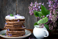 Chocolate pancakes and flowers, breakfast. Royalty Free Stock Photo