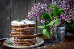 Chocolate pancakes and flowers, breakfast. Stock Photo