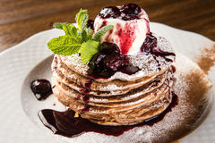 Chocolate Pancakes with Vanilla Ice Cream and Warm Cherry Sauce on white plate Stock Image