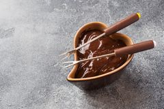 Chocolate paste with cinnamon and anise. Fondue with chocolate on a dark concrete table.  royalty free stock image