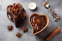 Chocolate paste with cinnamon and anise. Fondue with chocolate on a dark concrete table.  royalty free stock photo