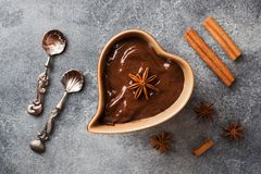 Chocolate paste with cinnamon and anise. Fondue with chocolate on a dark concrete table. copy space. Chocolate paste with cinnamon and anise. Fondue with royalty free stock photography