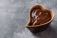 Chocolate paste with cinnamon and anise. Fondue with chocolate on a dark concrete table. copy space. Chocolate paste with cinnamon and anise. Fondue with stock photography