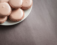 Chocolate pastel brown Macarons or Macaroons on a plate stock image