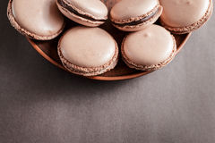 Chocolate pastel brown Macarons or Macaroons on a plate royalty free stock photography