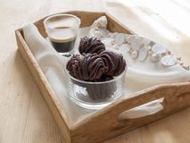 Chocolate pastries with espresso. Close up of some chocolate puddings, in glass bowl. The bowl is on a wooden tray with a beige placemat. On the back a cup of Stock Photography