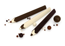 Chocolate pencils and balls on white background Stock Photos