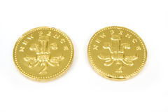Chocolate penny coins. Closeup of two gold colored British chocolate penny coins, isolated on white background Royalty Free Stock Image