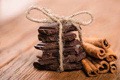 Chocolate pieces and cinnamon sticks Royalty Free Stock Images