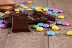 Chocolate pieces with color smarties on wooden board. Horizontal photo with heap of dark chocolate pieces on wooden board with colorful chocolate sweet smarties Stock Photo