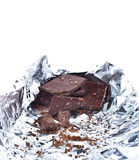 Chocolate pieces crumpled in foil on white background Stock Images