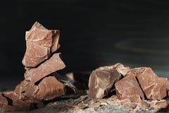 Chocolate pieces on a dark backround. Handmade chocolate pieces in a spotlight on a dark wooden backround Royalty Free Stock Image