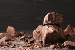 Chocolate pieces on a dark backround. Handmade chocolate pieces on a dark wooden backround Royalty Free Stock Images