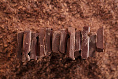 Chocolate pieces on grated chocolate background Royalty Free Stock Photo