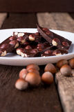 Chocolate pieces with hazelnut nuts on white plate wooden background. Royalty Free Stock Photos