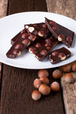 Chocolate pieces with hazelnut nuts on white plate wooden background. Stock Image