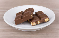 Chocolate pieces with hazelnuts in saucer Stock Photos