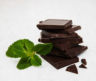 Chocolate pieces with a leaf of mint. On white wooden background Royalty Free Stock Photo
