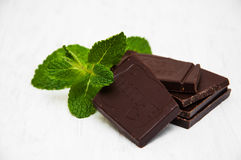 Chocolate pieces with a leaf of mint. On white wooden background Royalty Free Stock Photography