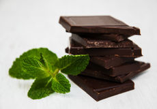 Chocolate pieces with a leaf of mint. On white wooden background Stock Photography
