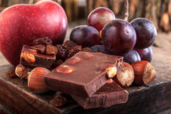 Chocolate pieces with nuts grapes and apple Royalty Free Stock Image
