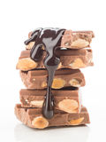 Chocolate pieces tower flooded with liquid chocolate on white Royalty Free Stock Photo