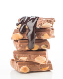 Chocolate pieces tower flooded with liquid chocolate on white Stock Photography