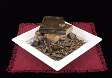 Chocolate Pile on White Plate and Burgandy Napkin. Pile of dark and milk chocolate on black background and white plate with chips, shavings and slivers Stock Image
