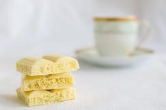 Chocolate poroso branco saboroso e xícara de café Imagens de Stock