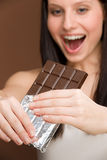 Chocolate - portrait young woman bite sweets Royalty Free Stock Images
