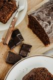Chocolate pound cake slices on white plates. Brown toned, wooden background. Chocolate bar broken into pieces stock photos